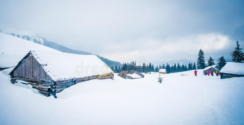 Panorama of wooden chalets in Carpathian mountains. Panoramic view of wooden chalets in Carpathian mountains surrounded with forest. Tourists walking to the stock photo