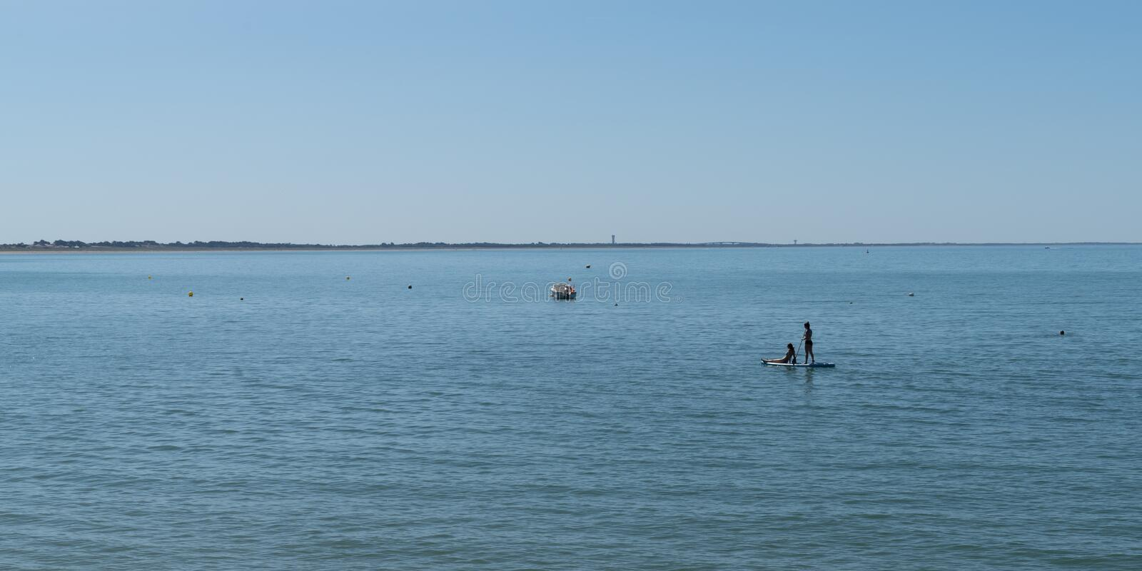 Panorama young girls on stand up paddle board sap in water sea beach summer season boat and ship vacation concept royalty free stock photography