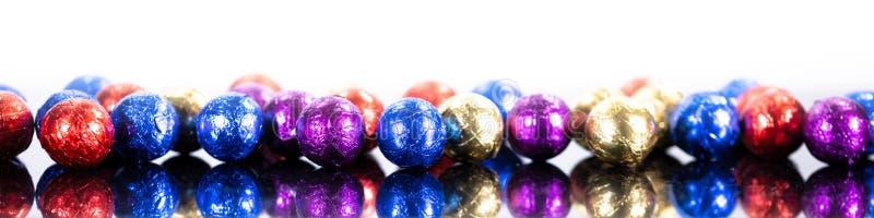 Panorama z kolorowymi czekoladowymi piłkami przed białym backgro obrazy royalty free