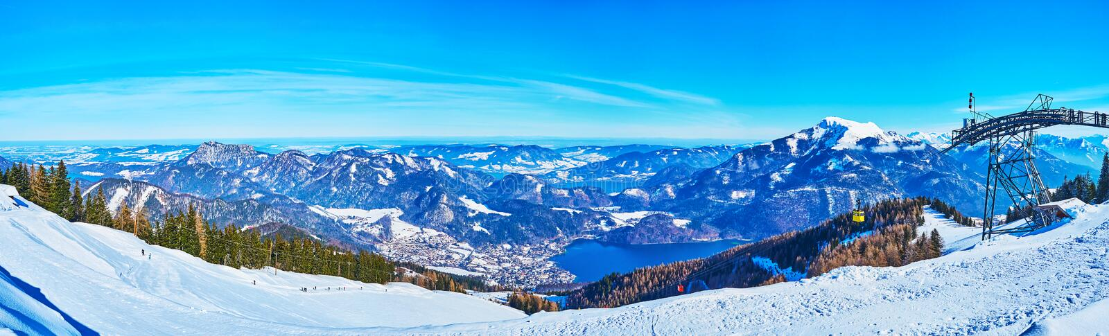 Panorama of Zwolferhorn mount and Wolfgangsee valley, St Gilden, Salzkammergut, Austria. Amazing winter panorama of Zwolferhorn mountain slopes, covered with ski royalty free stock image