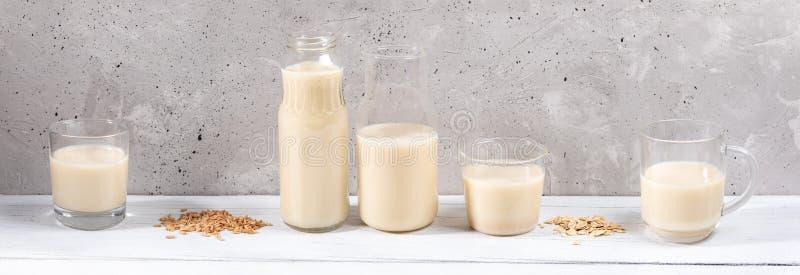 Panoramabilden av raden av exponeringsglasbehållare med havren mjölkar på den vita trätabellen på grå betongväggbakgrund royaltyfri fotografi