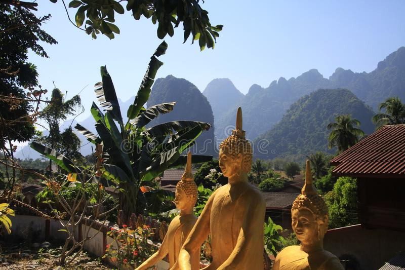 Panoramablick auf Karsthügellandschaft mit goldenen Buddha-Statuen von einem Tempel stockbilder