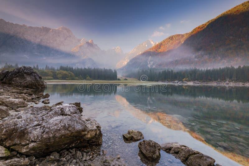 Panoramablick bei Sonnenaufgang ?ber alpinem See in Italien lizenzfreie stockfotos