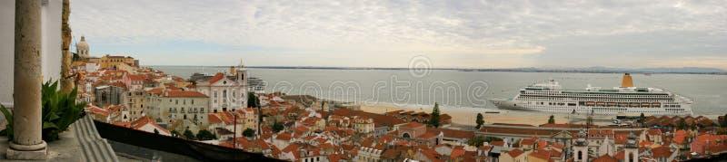 Panoramablick der Alfama Nachbarschaft und des Tajos in Lissabon, mit roten Dachspitzen und einem Kreuzschiff stockbilder