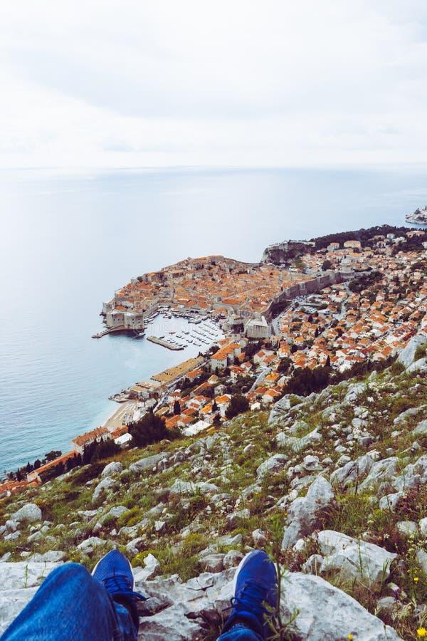 Panoramablick der alten Stadt von Dubrovnik vom Hügel, männliche Beine Kroatiens auf einem Felsen in einem Standpunkt stockbild