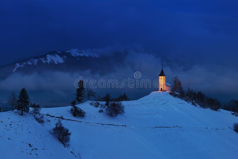Panoramablick der schönen Wintermärchenland-Gebirgslandschaft in den Alpen mit Pilgerfahrtkirche von Jamnik und von berühmtem Jul stockfoto