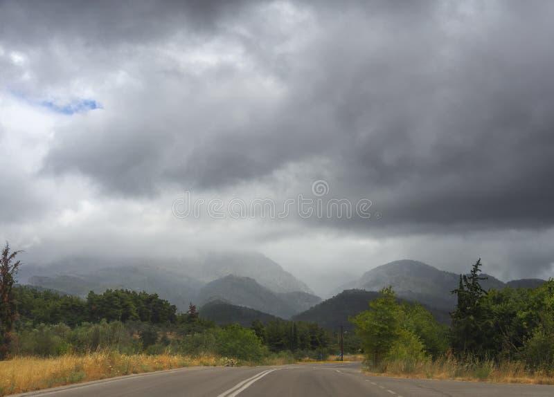 Panoramablick der Straße, des Waldes, der Berge und der Felder im griechischen Dorf auf der Insel von Evia in einem Sommersturm m stockfotografie