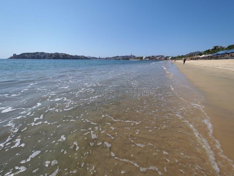 Panoramablick des sandigen Strandes an der Bucht von ACAPULCO-Stadt in Mexiko mit Touristen und an den ruhigen Wellen von Pazifis lizenzfreies stockbild