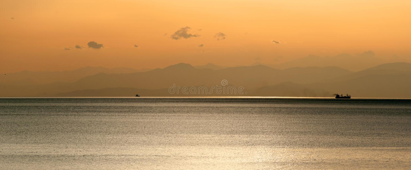 Panoramablick des Schiffs bei Sonnenuntergang mit Bergen stockbilder