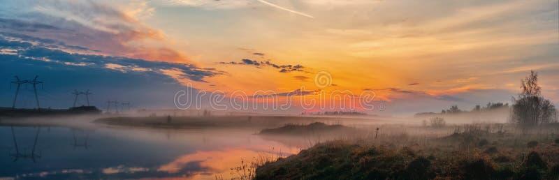 Panoramablick des Sonnenaufgangs über dem See, schöne Landschaft mit Morgennebel, atemberaubender Sommersonnenaufgang Die Schönhe lizenzfreie stockfotos
