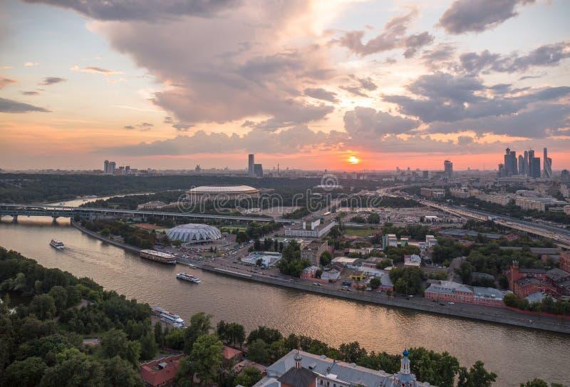 Panoramablick des Sonnenuntergangs über Moskau-Stadt- und -wolkenreflexionen im Fluss mit reisenden Booten lizenzfreies stockbild