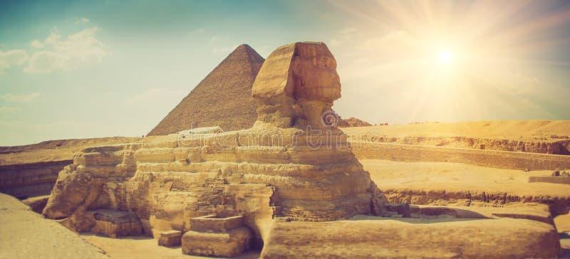 Panoramablick des vollen Profils der großen Sphinxes mit der Pyramide im Hintergrund in Giseh Egypt stockbilder