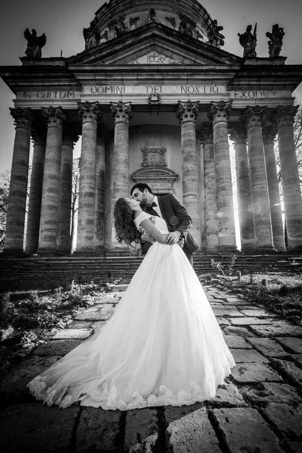 Panoramablick eines Märchenjungvermähltenpaares, das vor alter barocker ghotic Kirche umarmt und küsst stockfotografie