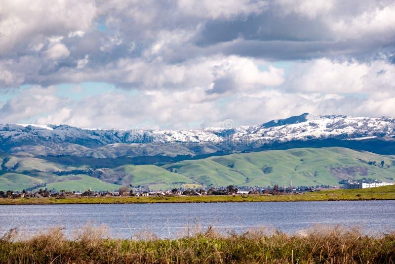 Panoramablick in Richtung in Richtung den grünen Hügeln und zu den schneebedeckten Bergen an einem kalten Wintertag genommen von  stockfotos