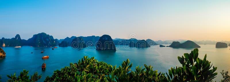 Panoramablick von den Booten, die in das ruhige Wasser von Halong-Bucht Vietnam bei Sonnenuntergang schwimmen stockfoto