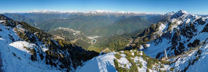 Panoramablick von der Spitze des Aibga-Gebirgszugs zum Skiort Rosa Khutor Das Tal wird durch Hochgebirge umgeben lizenzfreie stockbilder