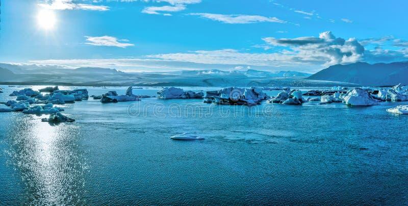 Panoramablick von Jokulsarlon-Gletscher See und Breidamerkurjokull glasiger am Hintergrund, der zur Sonne gegenüberstellt lizenzfreies stockfoto