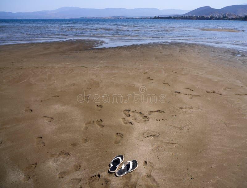 Panoramablicke des sandigen Strandes, der Berge und der Insel von Evia, der Flipflops und der Abdrücke im Sand bei Ebbe auf Lia lizenzfreie stockbilder