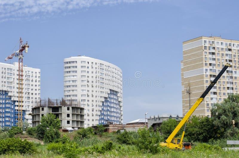 Panoramabouw Autokraan op de achtergrond van mooie gebouwen, groene ruimten en een blauwe hemel royalty-vrije stock foto's