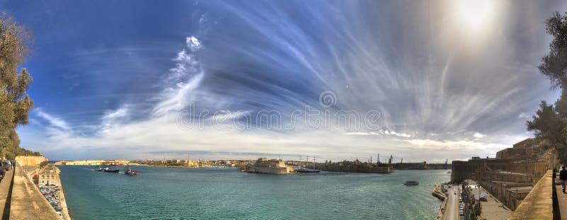 Panoramafoto av området för hamn för Valletta stad det storslagna på Malta, med många historiska byggnader längs kustlinjen arkivfoton