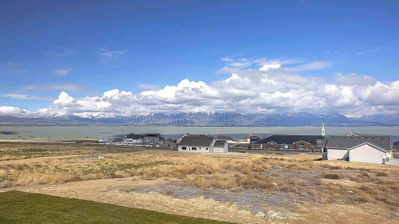 Panoramagrannskap med sikt av sjön och berget under molnig blå himmel på en solig dag royaltyfria foton