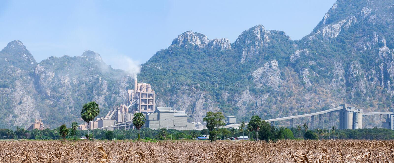 Panoramalandschaft der Zementfabrik in Thailand, Maisfeldvordergrund, Kalksteingebirgszughintergründe lizenzfreie stockfotografie