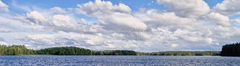 Panoramalandschaft mit drastischen Kumuluswolken in der hellen Sommertagesszene in Finnland stockbild