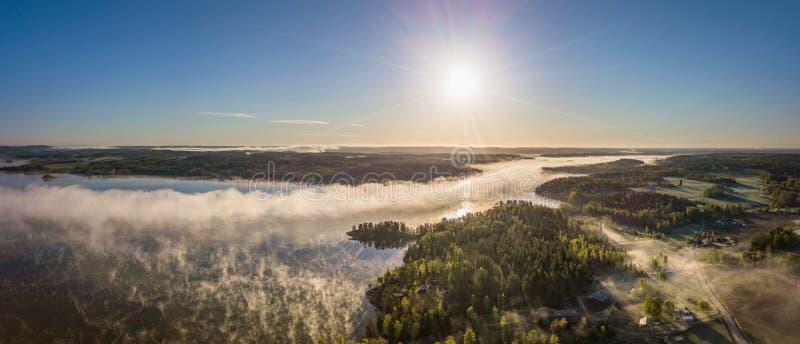 Panoramam di un'alba in un lago con nebbia fotografie stock libere da diritti