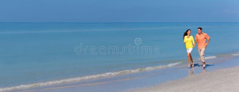Panoramaman- & kvinnapar som kör på en strand fotografering för bildbyråer