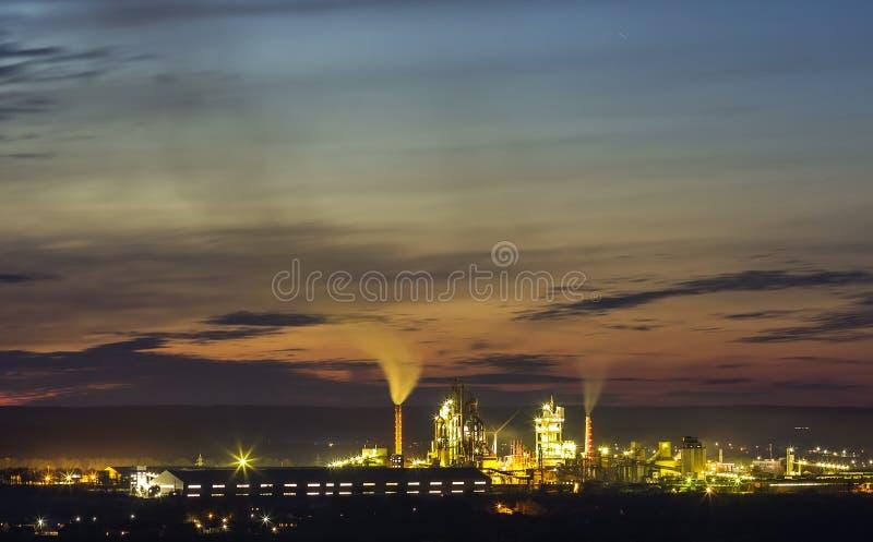 Panoramamening van cementinstallatie en machtssation bij nacht in Ivano stock afbeelding