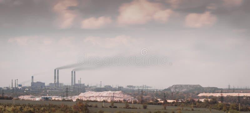 Panoramamening van de fabriek met rokende schoorstenen en de hemel met wolken in de Oekraïne Mariupol stock afbeeldingen