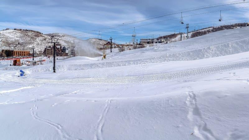 Panoramarampanoramautsikten av skidar semesterorten på ett berg som filt med snö royaltyfri bild