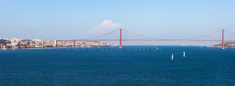 Panoramasikt över 25na de Abril Bridge Bron förbinder staden av Lissabon till kommunen av Almada royaltyfria bilder