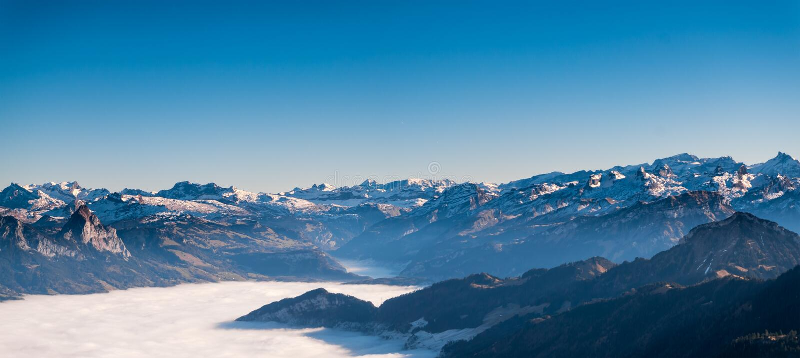 Panoramasikt av det schweiziska fjällängberget med mist/dimmigt i vintertiden royaltyfri bild