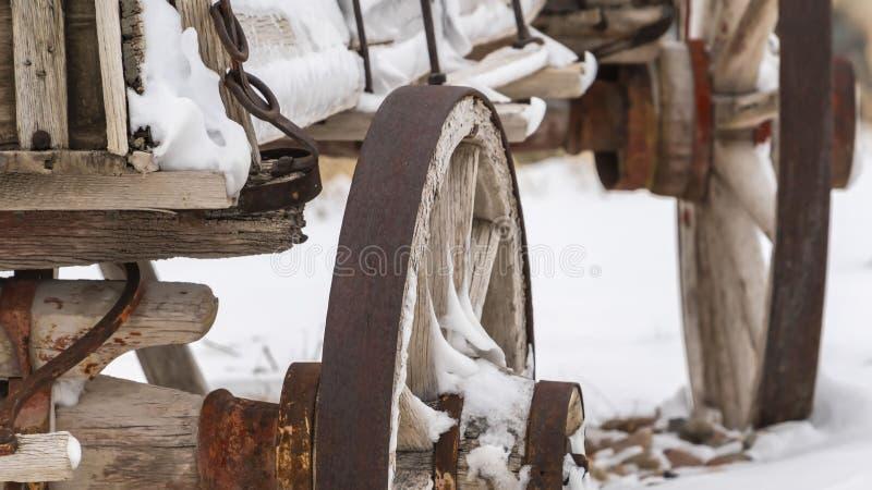 Panoramaslut upp av de rostiga hjulen av en gammal trävagn som beskådas i vinter royaltyfri fotografi