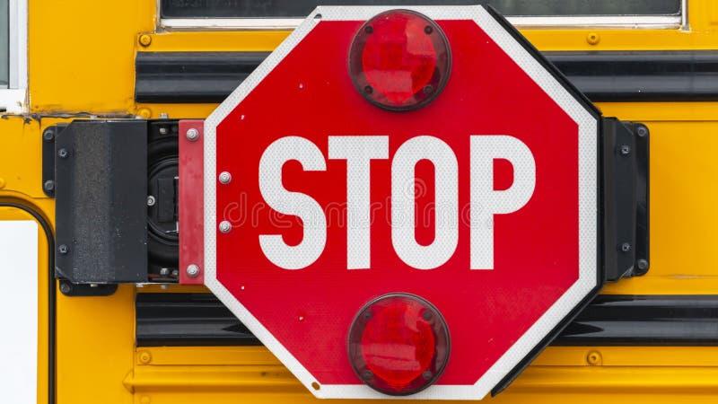 Panoramaslut upp av ett oktogon format rött stopptecken med signalljus på en skolbuss arkivbild