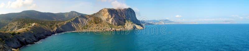 Panoramat av sommaren landskap med havet och bergskedja arkivbild