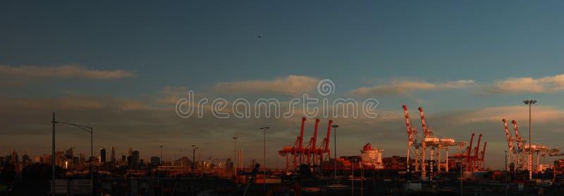 Panoramatiska vyer av långa portkranar som står höga och lastar ett fartyg i hamn med transportbehållare i Port Melbourne. arkivfoton