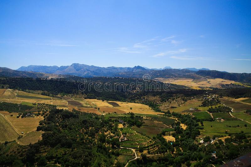 Panoramautsikt över den lantliga breda dalen som kontrasterar med molnfri blå himmel från den forntida byn Ronda - Andalusia, Spa arkivbild