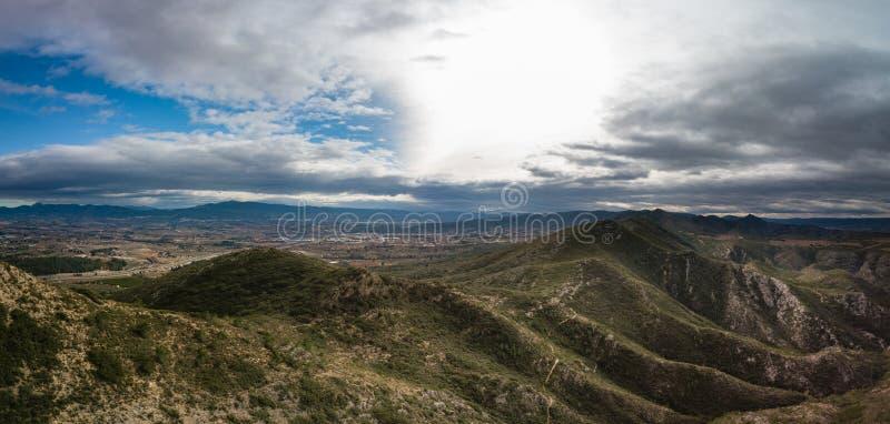 Panoramautsikt av berg med dramatiska himmel- och liten stadkanaler, Spanien i bakgrund royaltyfri fotografi