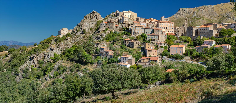 Panoramautsikt av bergbyn Speloncato Korsika arkivfoto