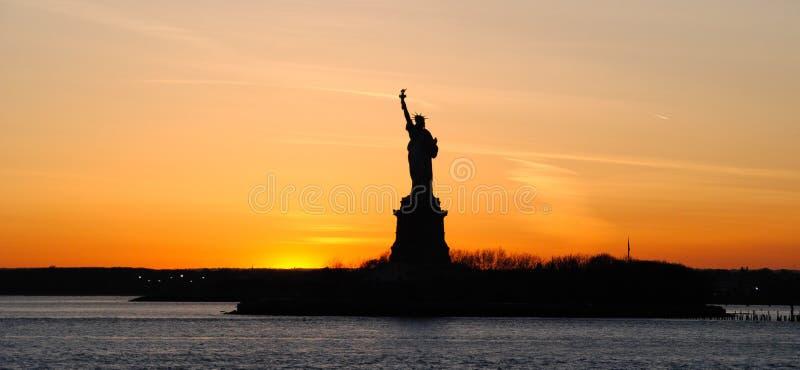 Panoramautsikt av den amerikanska symbolsstatyn av frihet, på solnedgången royaltyfri fotografi