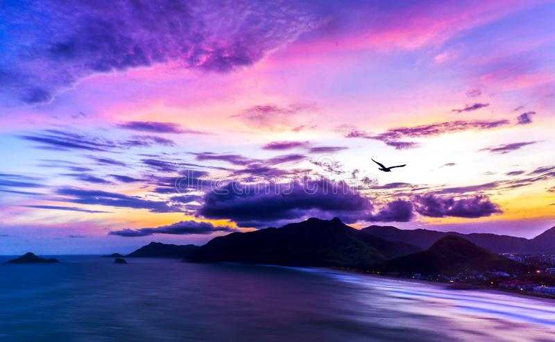 Panoramautsikt av den exotiska tropiska havö- och bergsolnedgången med långsamma vågor och purpurfärgad färgrik himmel med seagul arkivfoton