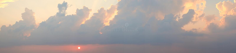 Panoramautsikt av den guld- gula inställningssolen och moln i ljus himmel - Skyscape arkivbilder