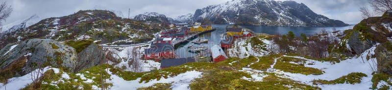 Panoramautsikt av den härliga snöig Nusfjord byn som tas från den höga kullen på Lofoten öar fotografering för bildbyråer