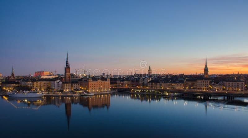 Panoramautsikt av den Stockholm staden på gryning, reflekterad över djupfryst vatten fotografering för bildbyråer