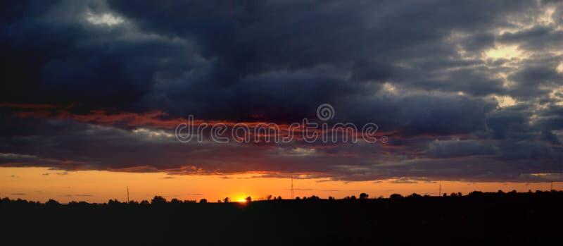 Panoramautsikt av den stunningly härliga sommarsolnedgången i det öppna fältet royaltyfri foto