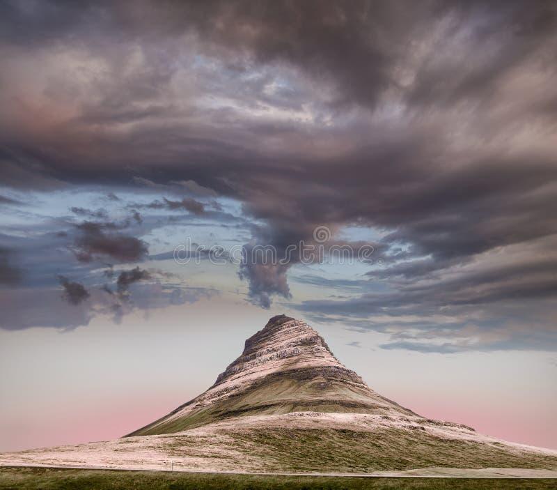 Panoramautsikt av det Kirkjufell berget under tunga moln royaltyfri fotografi