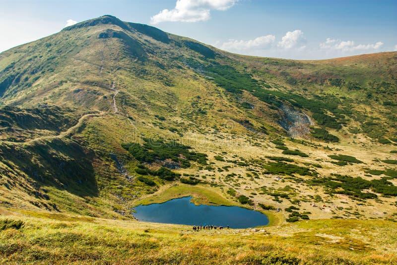 Panoramautsikt av en bergsjö i en dal för stenigt berg Fridfull sjö Berbeneskul, Carpathians, Ukraina arkivfoton