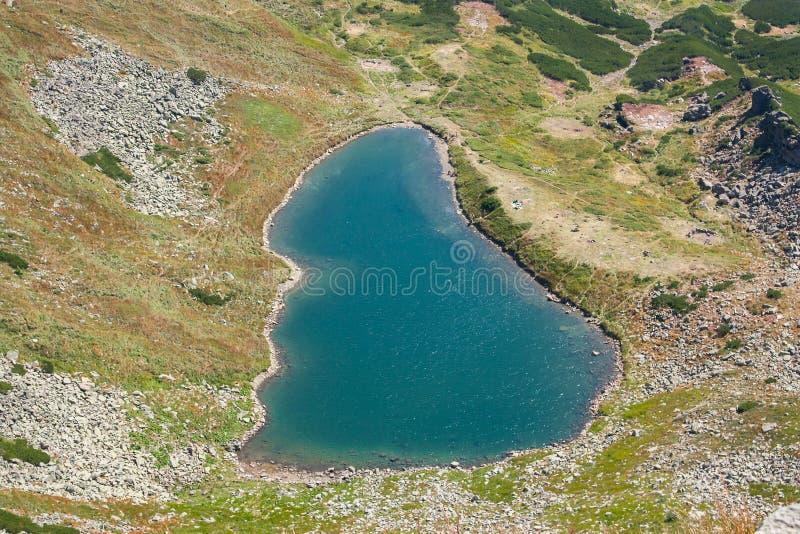 Panoramautsikt av en bergsjö i en dal för stenigt berg Fridfull sjö Berbeneskul, Carpathians, Ukraina royaltyfri bild